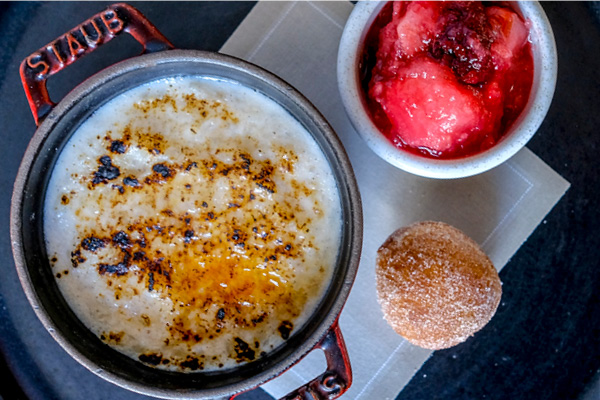 Baked rice pudding with cider, apple and bramble compote and cinnamon doughnut